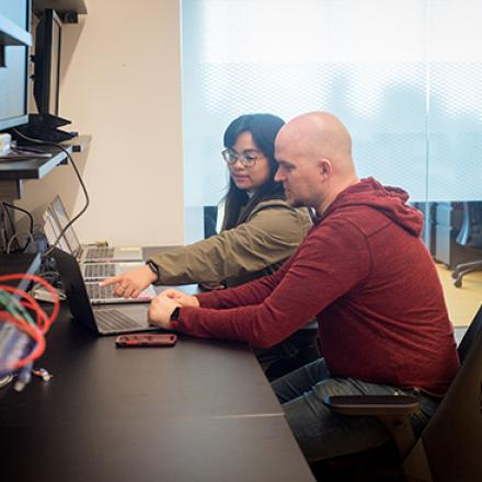 Two people working together at a laptop