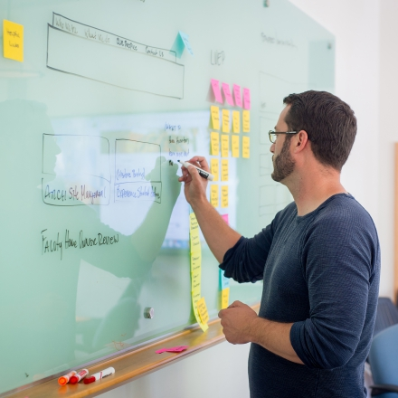 User Experience professional writing on markerboard