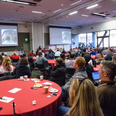Large group of audience looking at a presentation on two screens