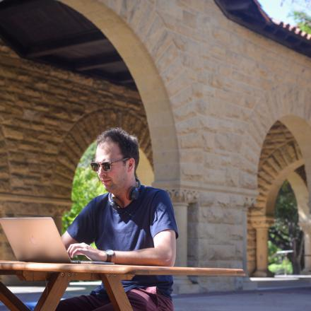 Stanford person outside on laptop