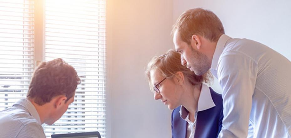 Three people looking at a gantt chart