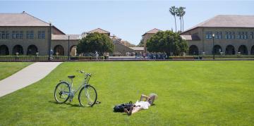 Woman lying in grass alongside bike