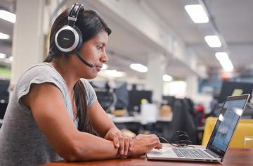 Woman with headset looking at laptop