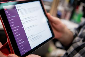 Person holding tablet with Slack on screen